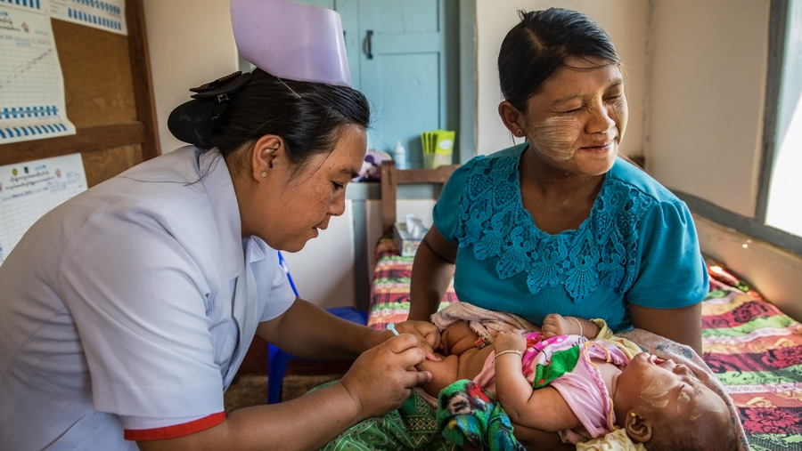 Myanmar:  A mother winces in sympathy pain as Midwife Daw Cho Thae vaccinates her child at the Health Center in Pindaya township. For many women, midwives are the primary point of contact for mothers with the healthcare system and they become trusted voices that help women in the transition to motherhood. ©UN0337712/Nyan Zay Htet