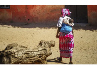 A woman walks with her baby in Dakar, Senegal. Photo by: Vince Gx on Unsplash